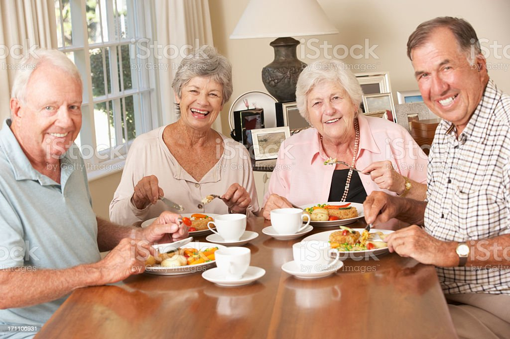 Group Of Senior Couples Enjoying Meal Together stock photo