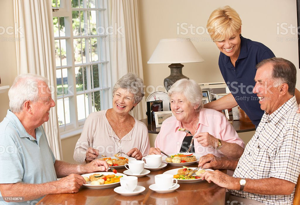 Group Of Senior Couples Enjoying Meal Together With Home Help stock photo