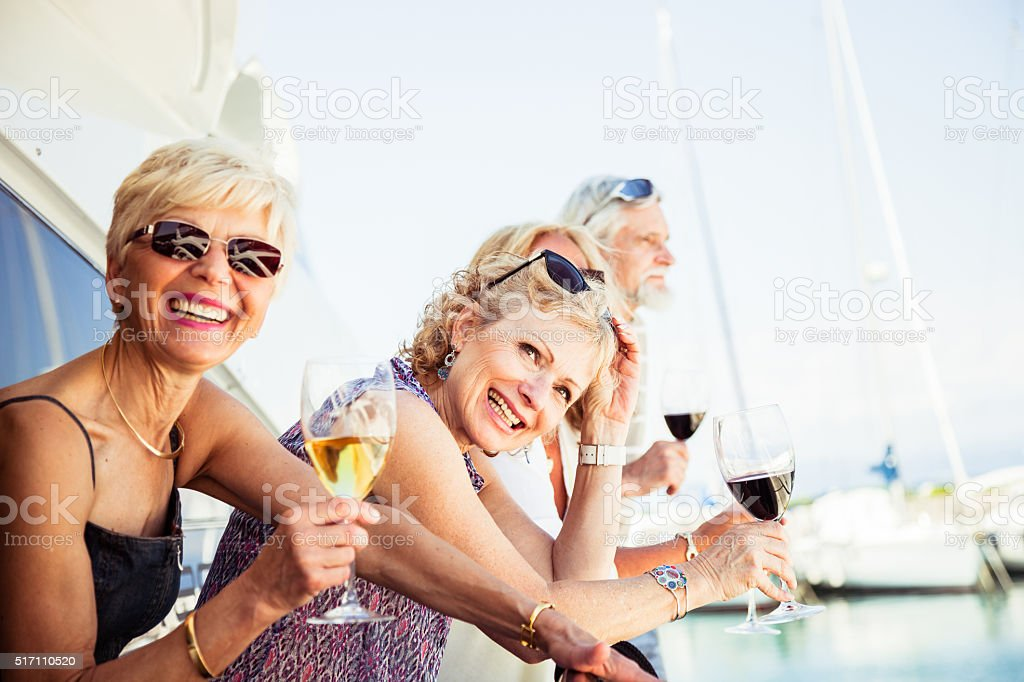 Group of senior friends drinking wine on a yacht stock photo
