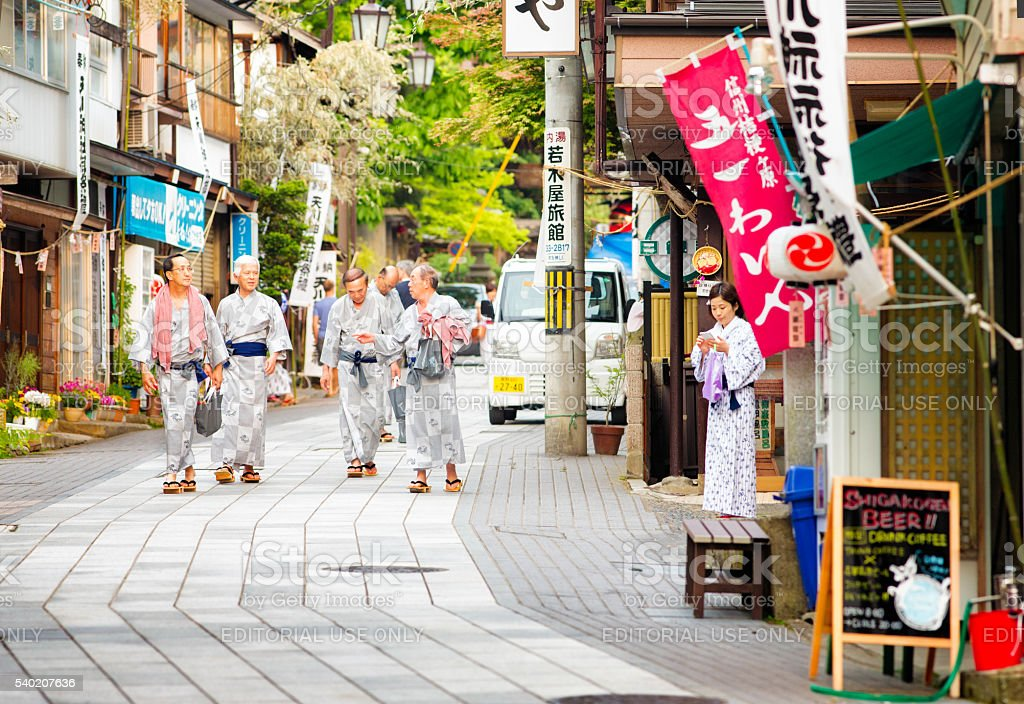 Group of senior Japanese men walking to Onsen wearing Yukatas stock photo