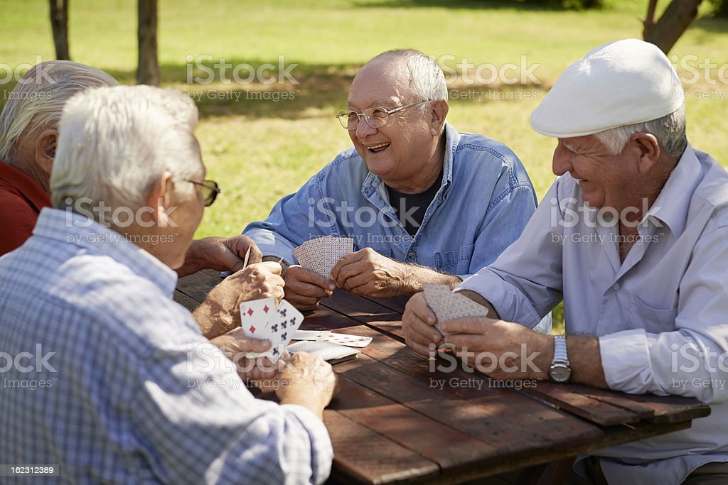 Group of senior men, smiling and playing cards at the park stock photo