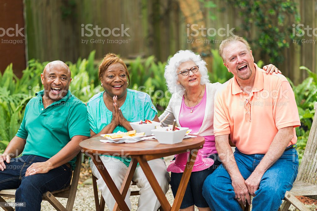 Group of seniors eating and laughing outdoors stock photo