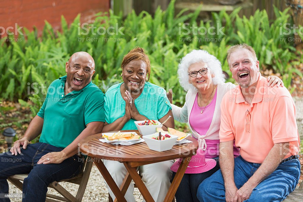 Group of seniors enjoying food and friends in back yard stock photo