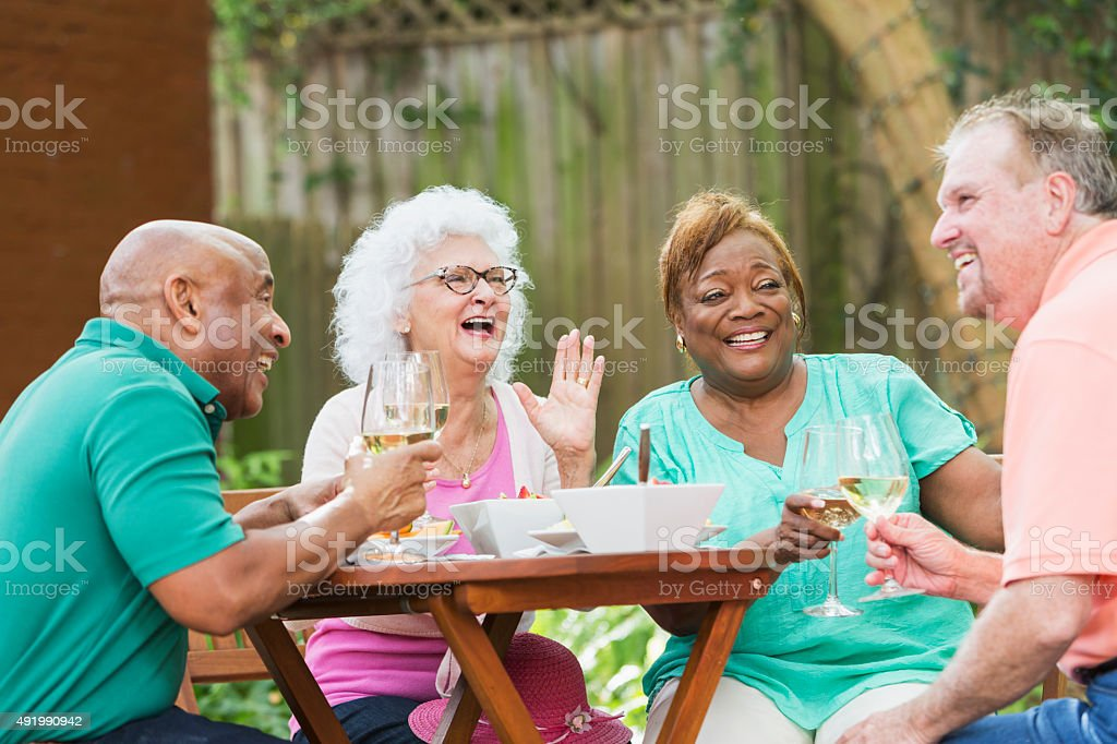 Group of seniors enjoying wine and food in back yard stock photo