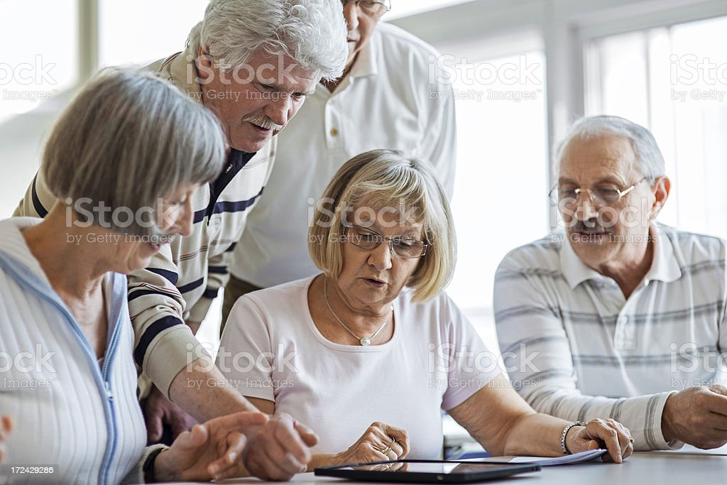 Group of seniors examine digital tablet stock photo