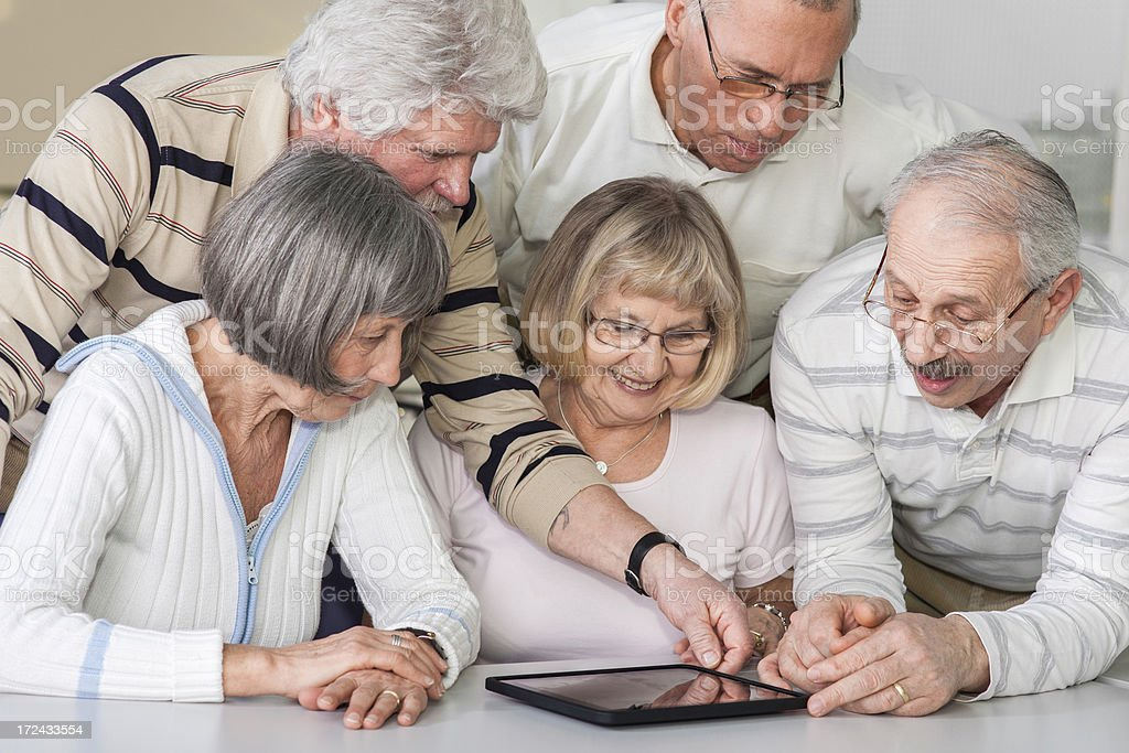Group of seniors examine digital tablet royalty-free stock photo