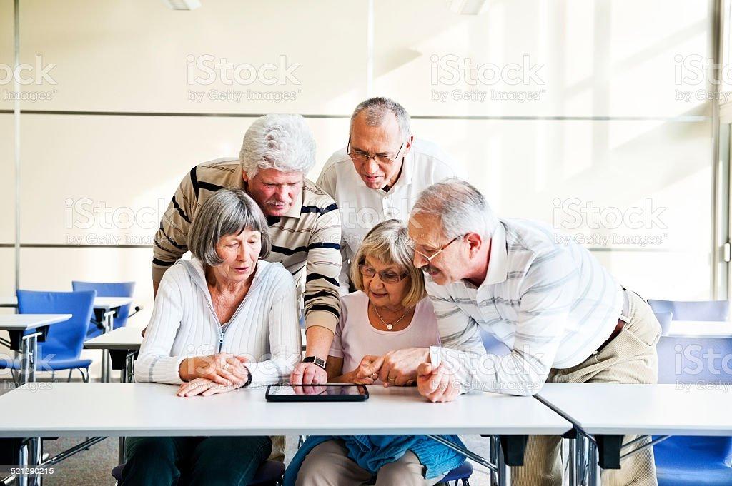Group of seniors examine digital tablet stock photo