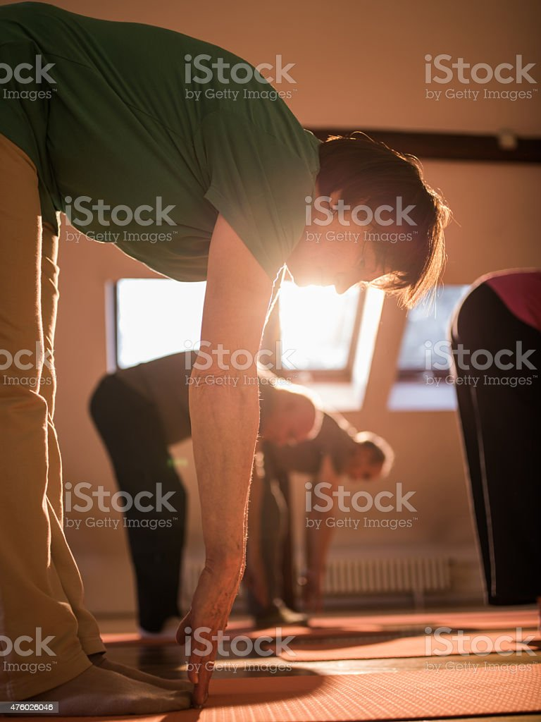 Group of seniors exercising while trying to touch the toes. stock photo