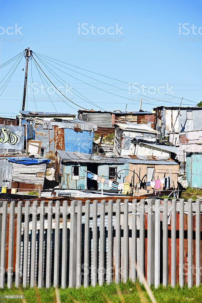 Group of shacks behind concrete fence, Khayelitsha, South Africa. stock photo
