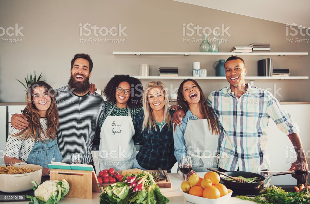 Group of six adults at food preparation table stock photo