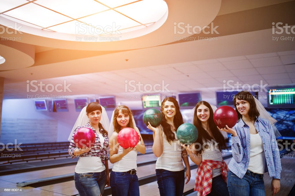 Group of six girls wit bowling balls at hen party on bowling club. stock photo