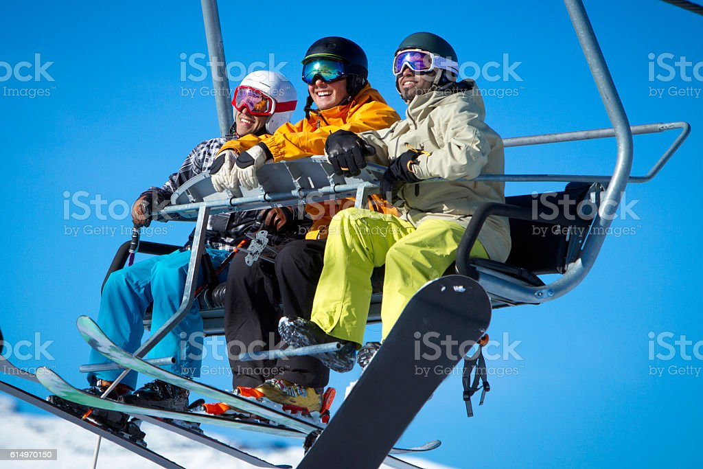 Group of skiers and snowboarders on chair lift. stock photo