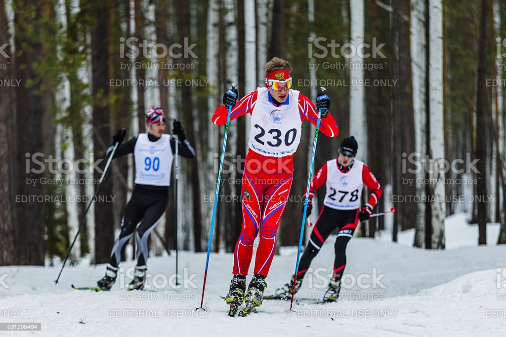 group of skiers male athletes running through woods stock photo