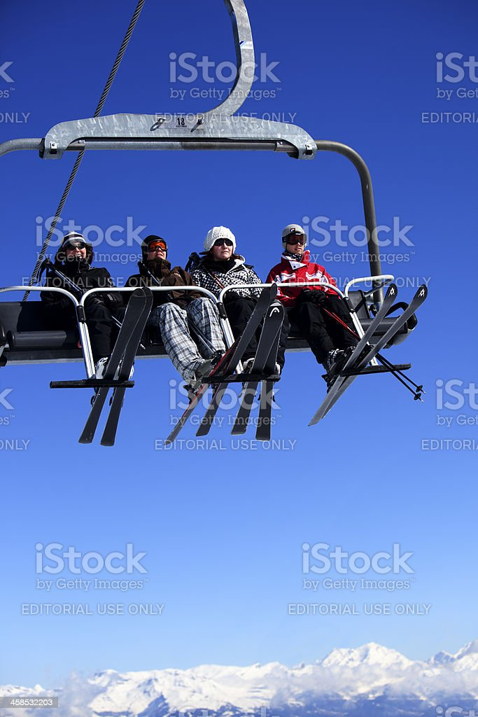 group of skiers on chair lift in the Swiss Alps royalty-free stock photo
