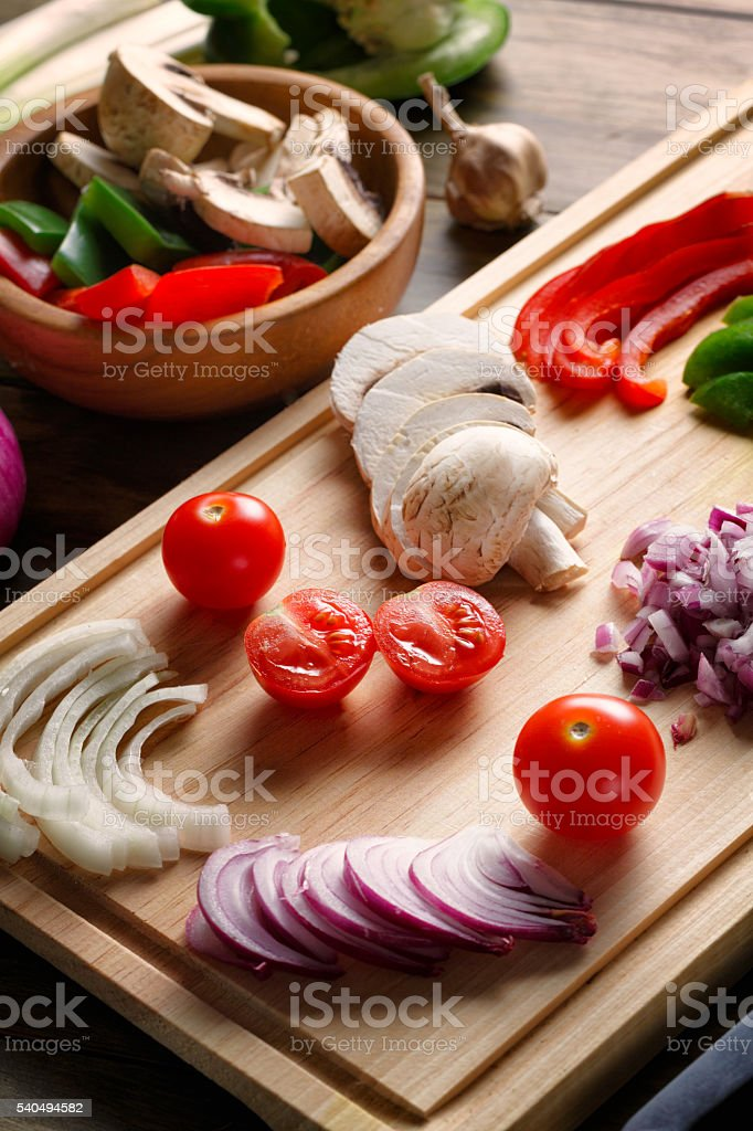 Group of sliced vegetables, on cutting board, ready for cooking stock photo