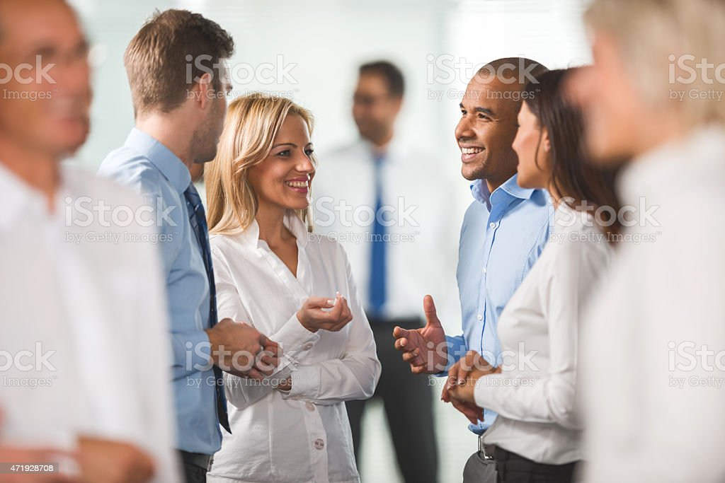 Group of smiling business people standing and communicating. stock photo