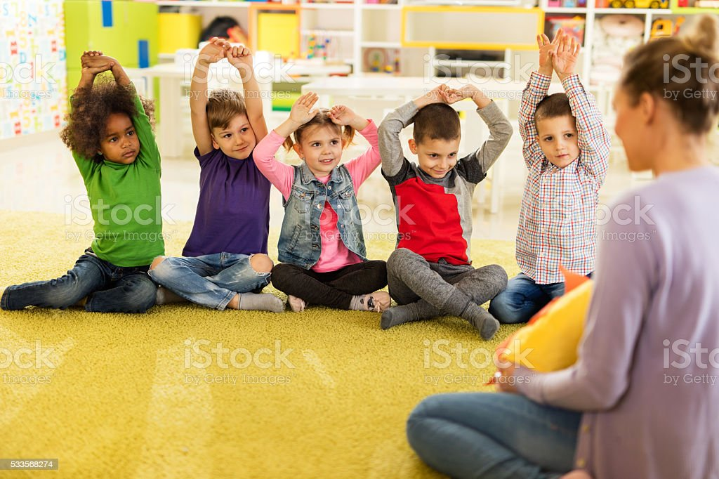 Group of smiling children having fun with teacher at preschool. stock photo