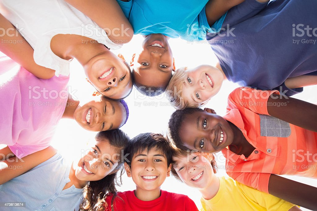 Group of smiling children in a circle staring down stock photo