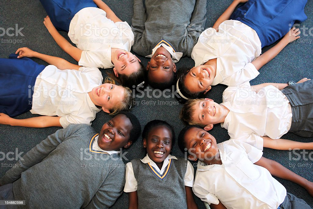 Group of smiling children lying in a circle stock photo
