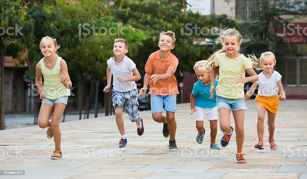 Group of smiling children running together in town on summer stock photo