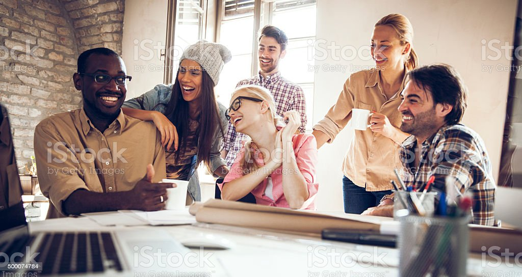 Group of smiling designers relaxing stock photo