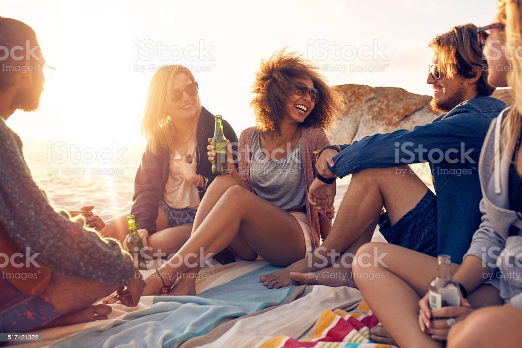 Group of smiling friends chilling on the beach stock photo