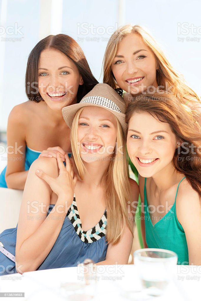 group of smiling girls in cafe on the beach stock photo