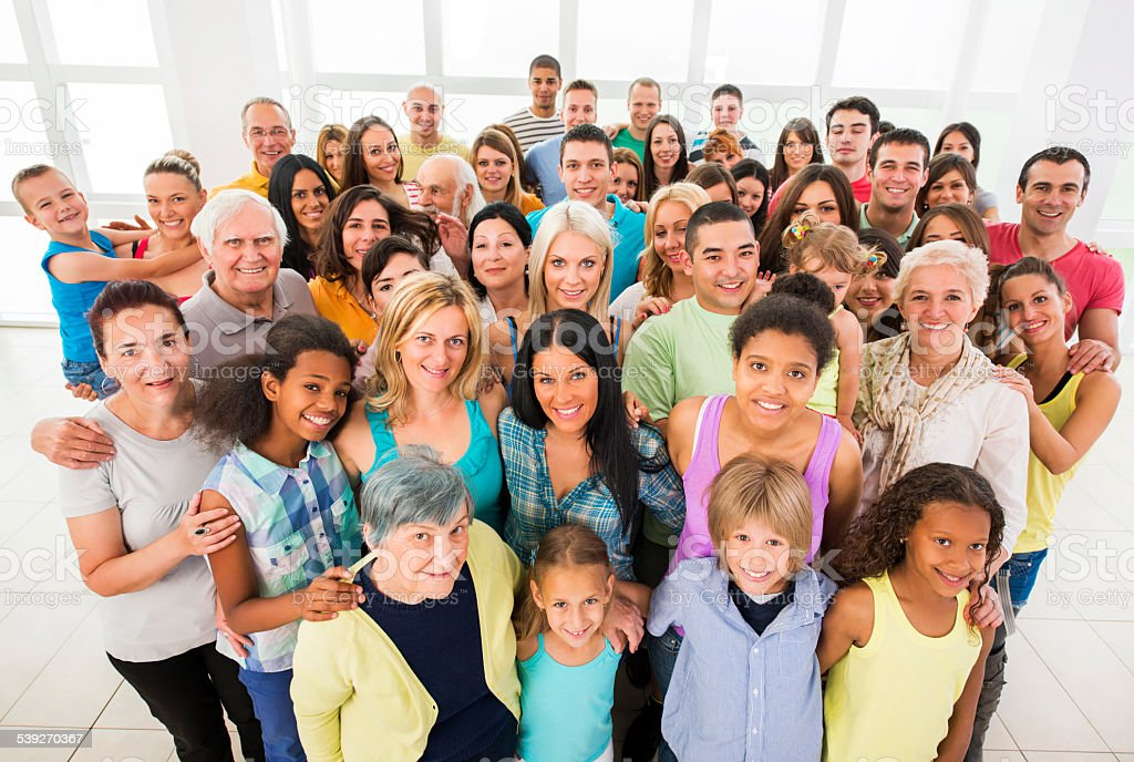 Group of smiling people embracing and looking at the camera. stock photo