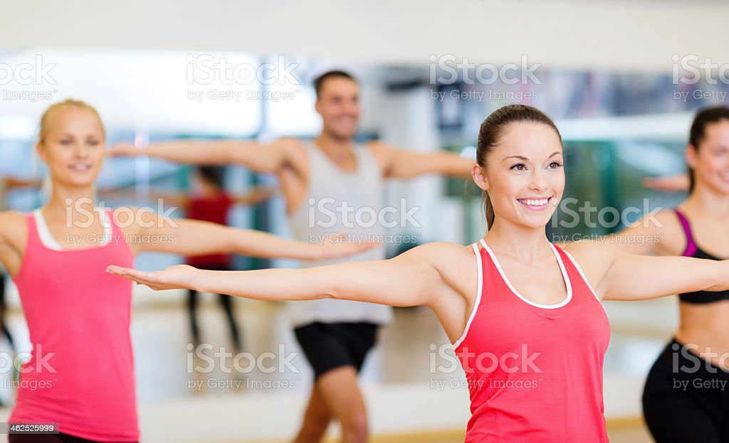 group of smiling people exercising in gym stock photo