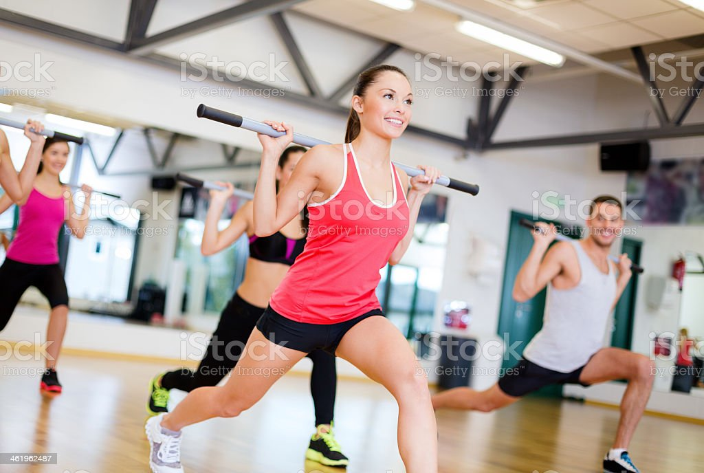 group of smiling people exercising with barbells in gym stock photo