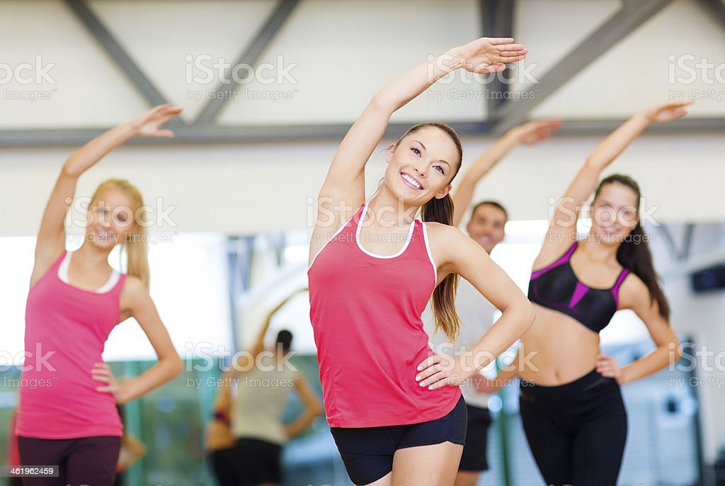 group of smiling people stretching in gym stock photo