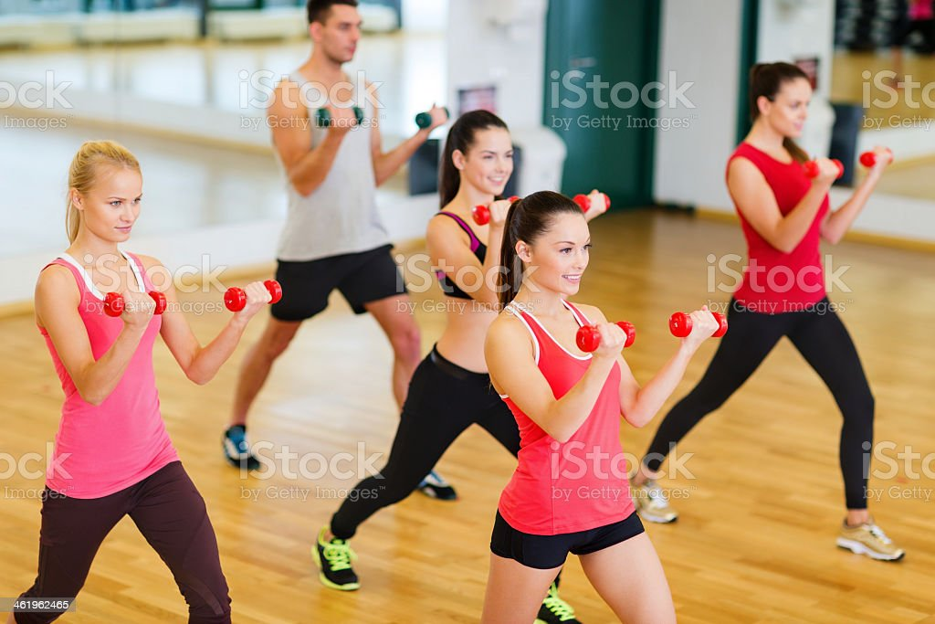 group of smiling people working out with dumbbells in gym stock photo