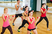 group of smiling people working out with dumbbells in gym