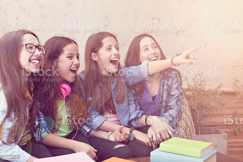 group of smiling pupils staying together and pointing up stock photo