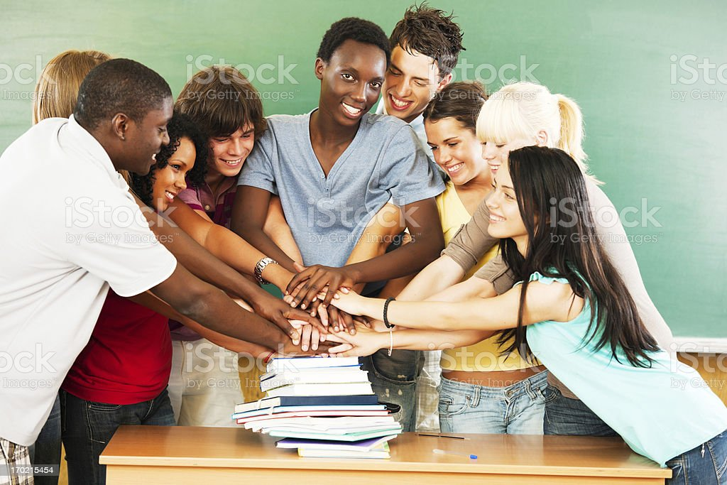 Group of smiling students with their hands pilled on books. royalty-free stock photo