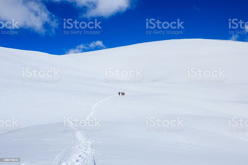 group of snowboarders climbing snow mountain and blue sky stock photo