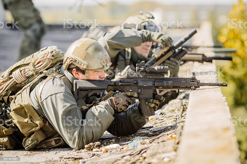 group of soldiers lie and shoot stock photo