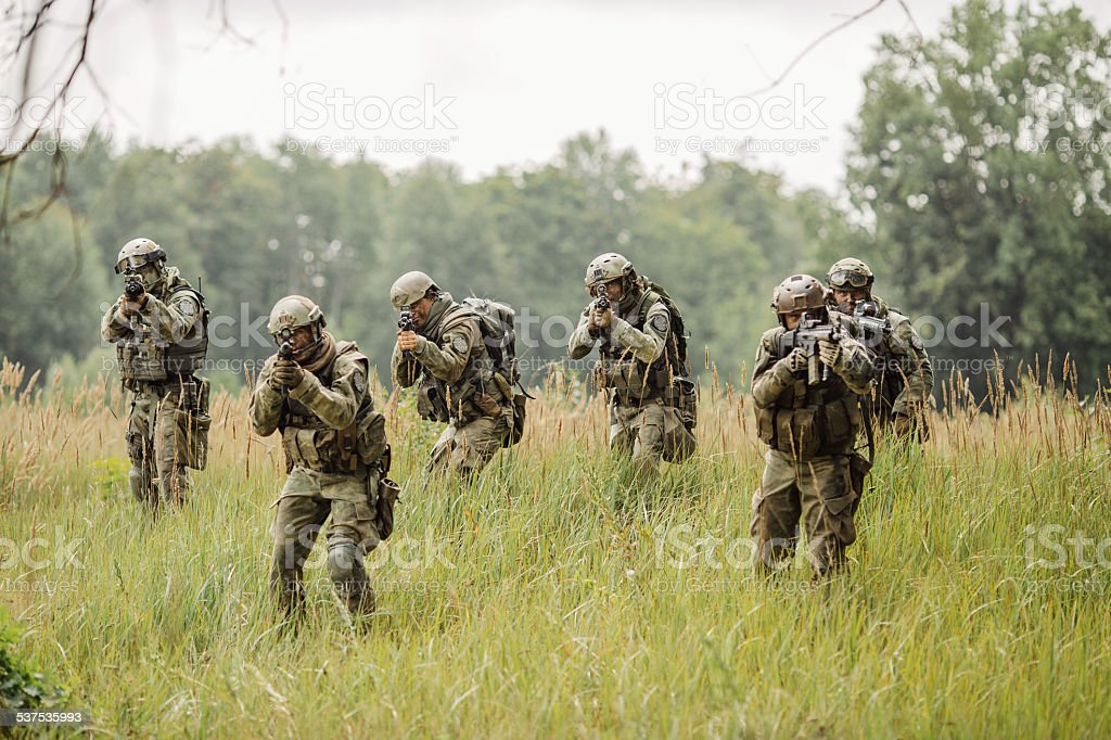 group of soldiers running across the field and shoot stock photo