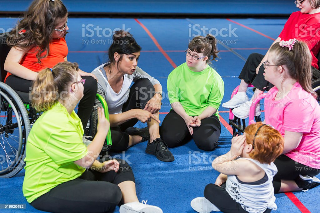 Group of special needs girls with instructor in gym stock photo