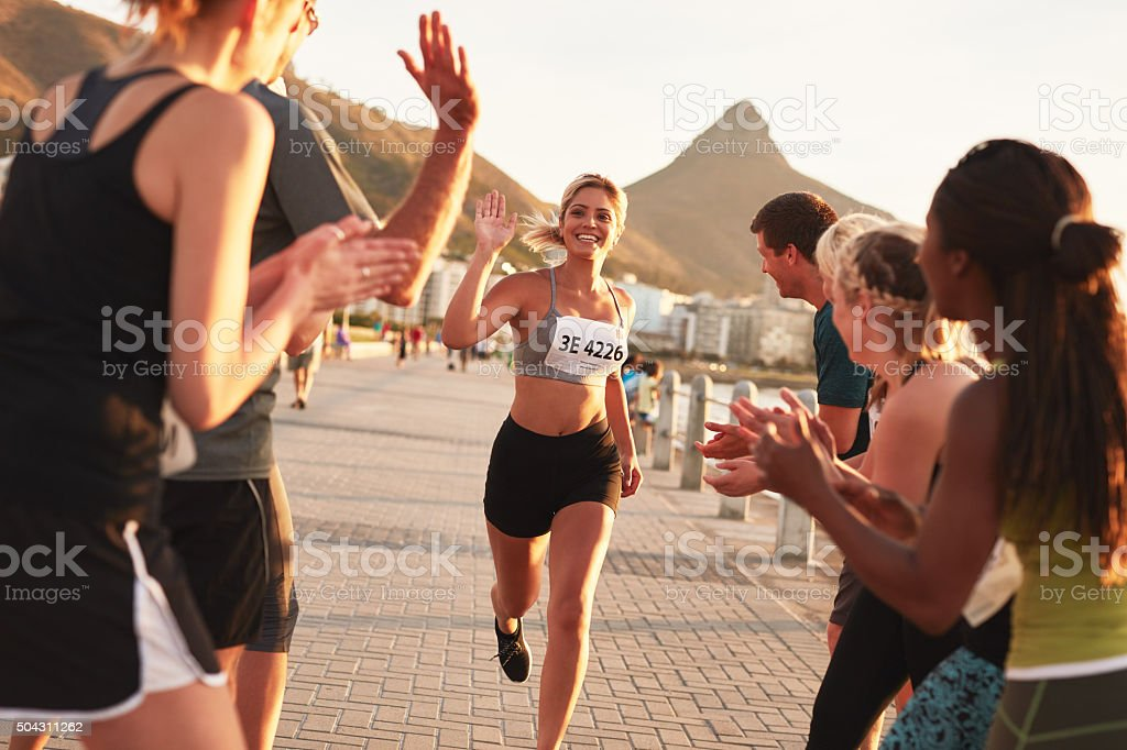 Group of spectators cheering runners at finish line stock photo