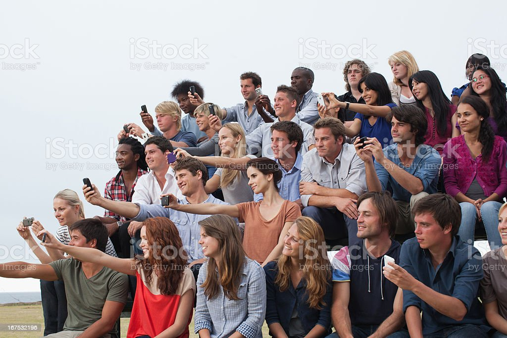 Group of spectators taking photographs stock photo