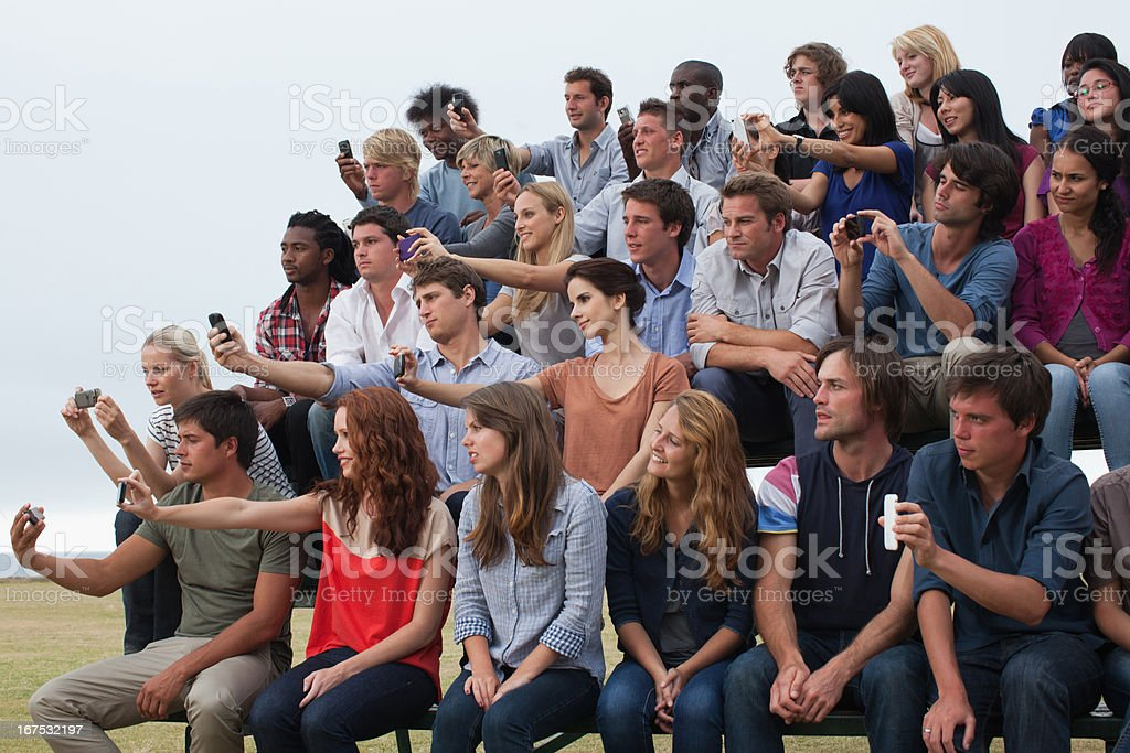 Group of spectators taking photographs royalty-free stock photo