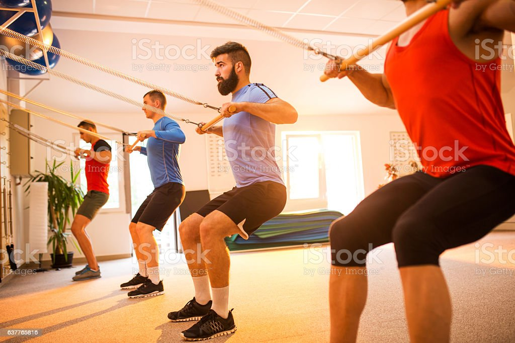 Group of sportsmen exercising on Pilates machines in health club. stock photo