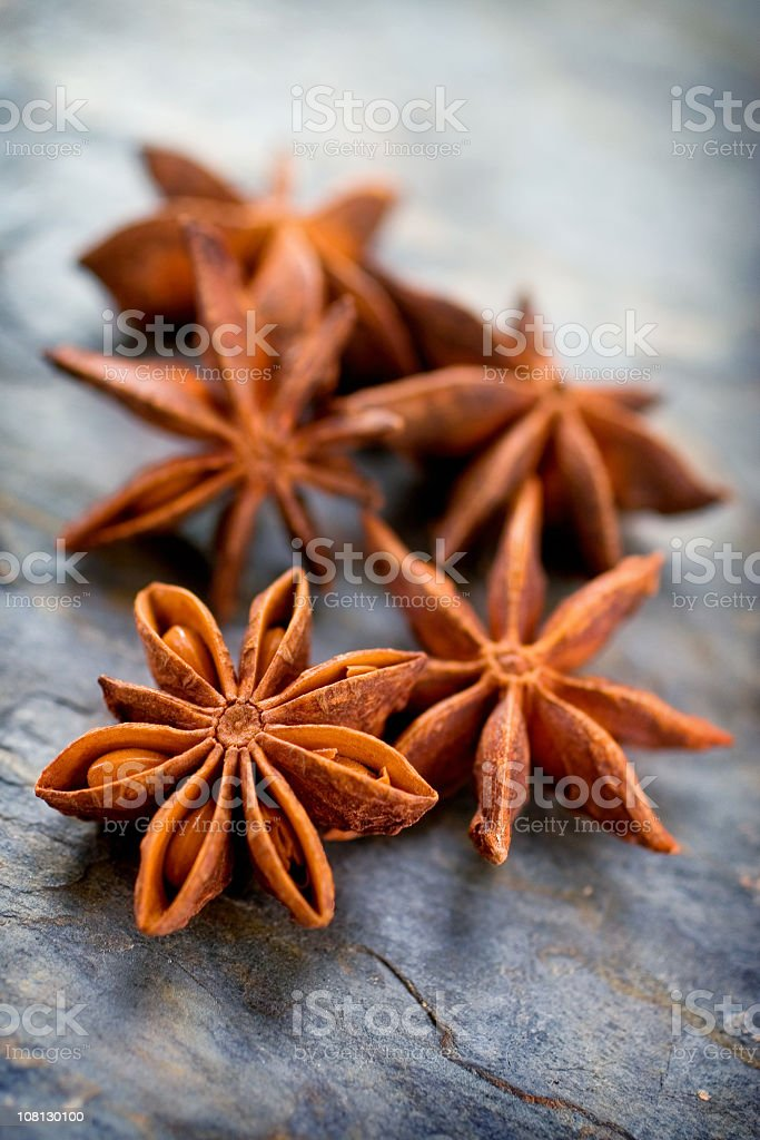 A group of star anise on a plain background royalty-free stock photo