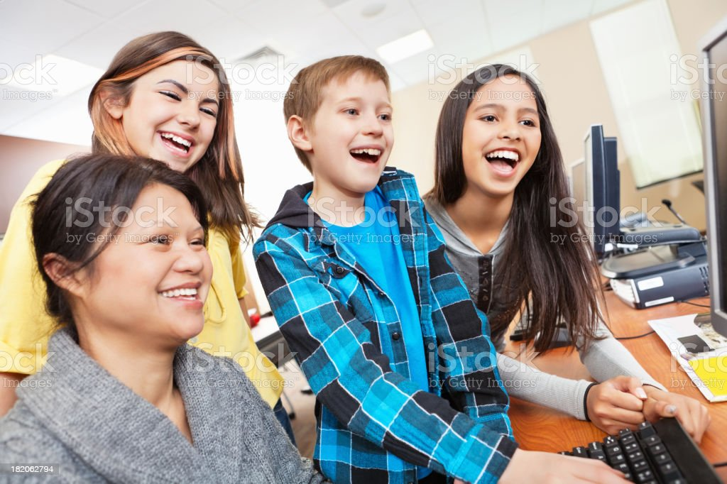 Group of students at a school computer laughing with teacher royalty-free stock photo