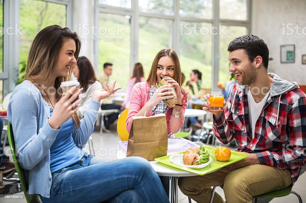 Group of students communicating during lunch in cafeteria. stock photo