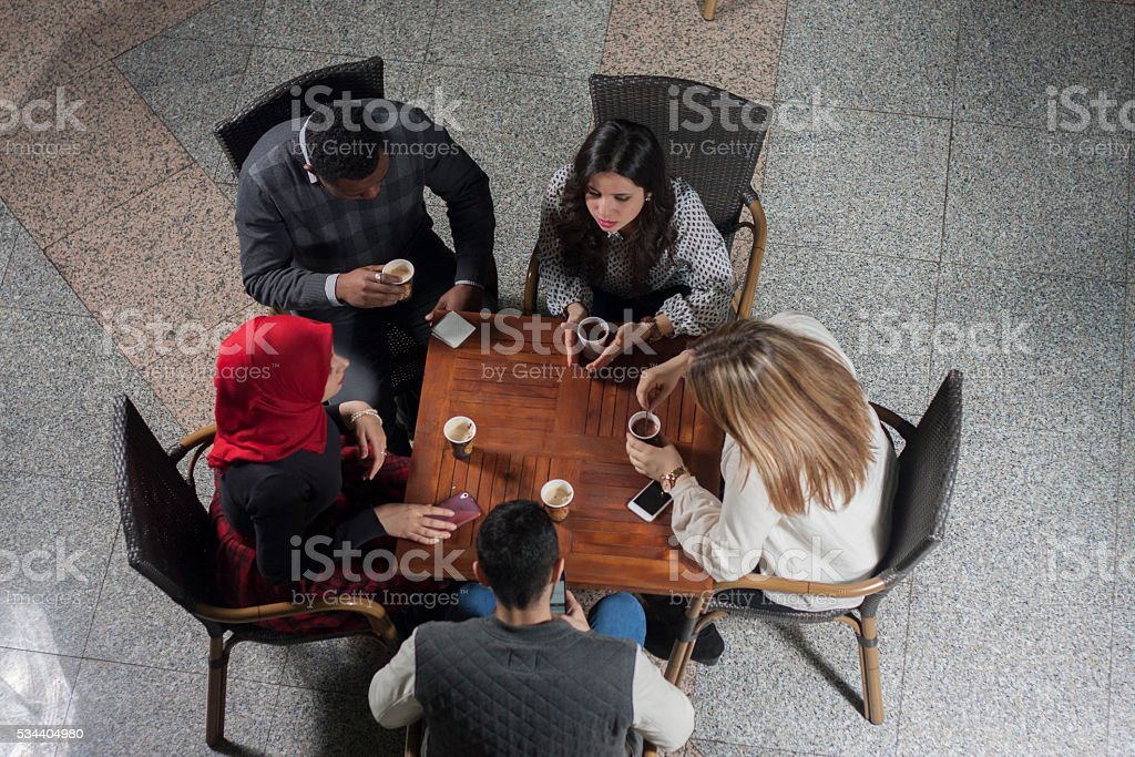 Group of students drinking coffee at university cafe stock photo