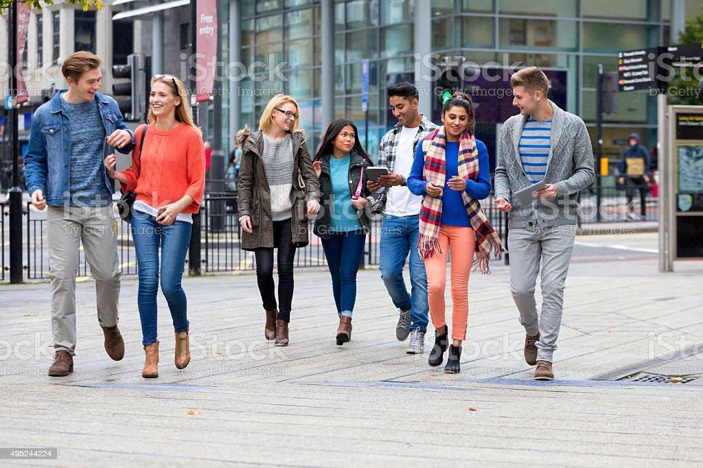 Group of mixed ethnic university students happily walking through...