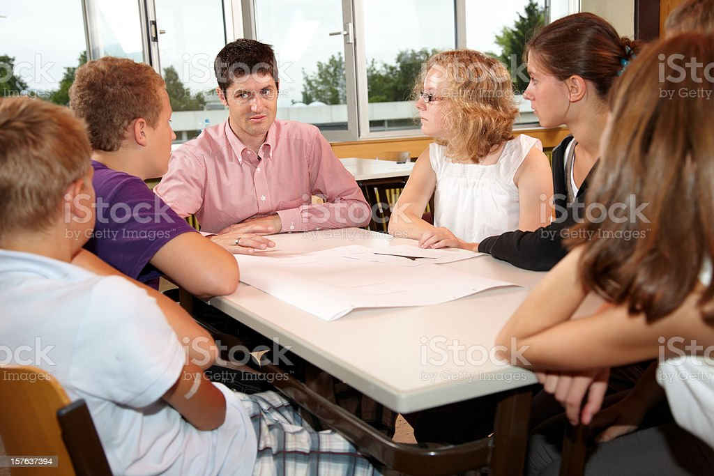 A group of students gather around a table for discussion stock photo