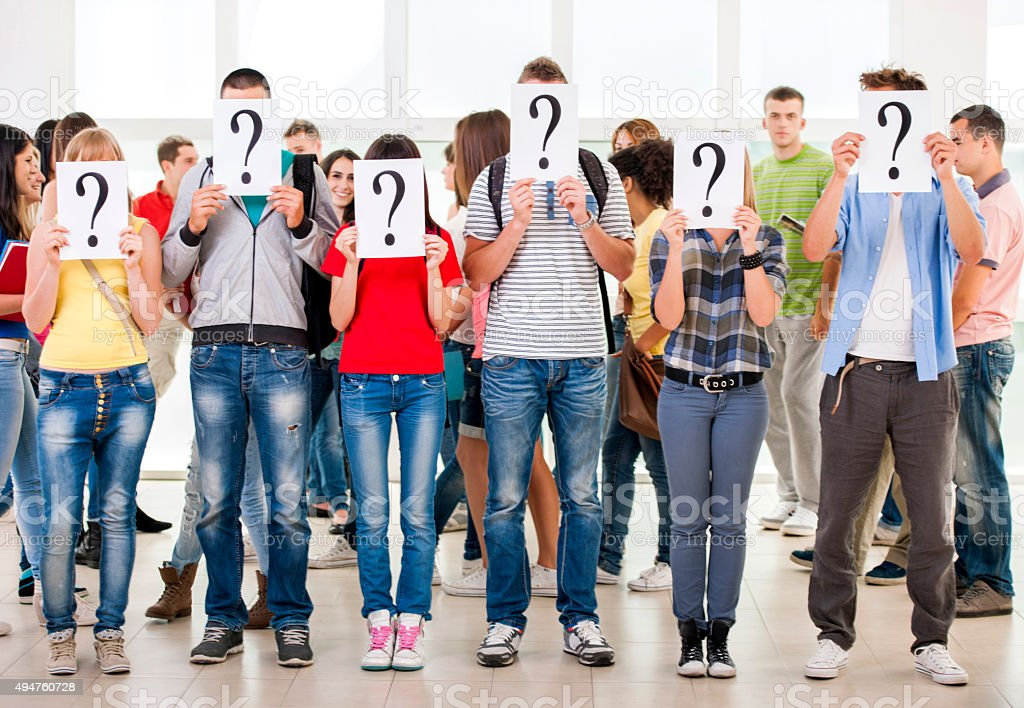 Group of students hiding their faces with question mark sign. stock photo